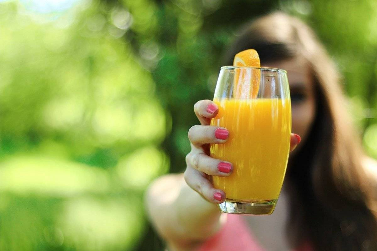 A woman holds out a glass of orange juice.