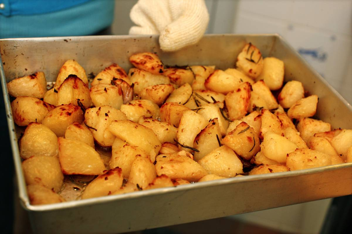 A chef holds a pan of roasted potatoes.