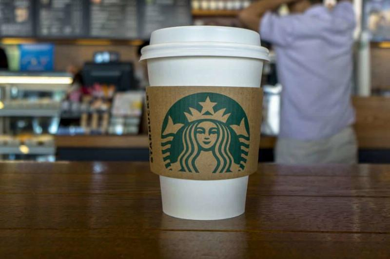 A to-go Starbucks cup is pictured on a table.