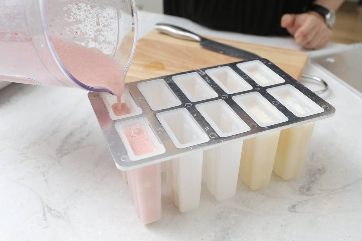 A woman pours strawberry banana yogurt into popsicle molds to freeze.