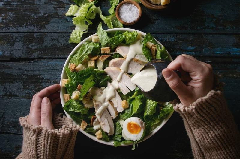 A woman pours Caesar dressing on a salad.