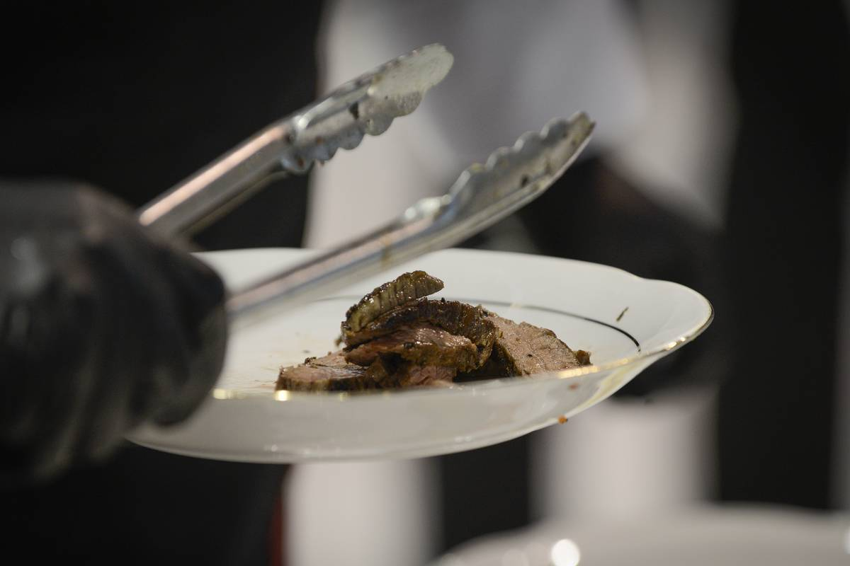 A chef carries steak and tongs in a plate.