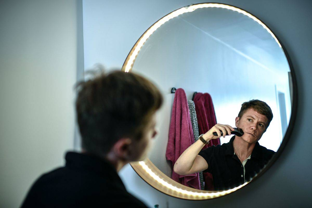 A man shaves his face while looking into the mirror.