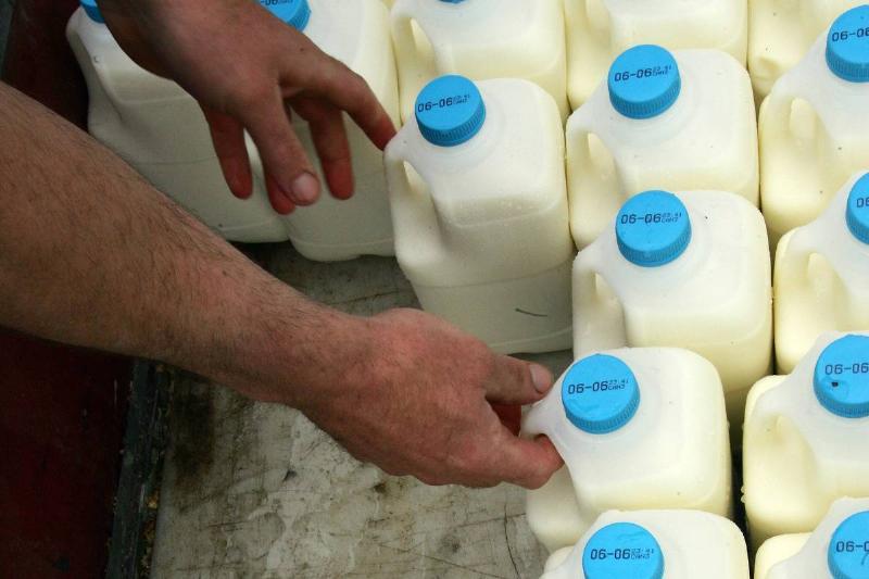 A man grabs cartons of milk from a truck.
