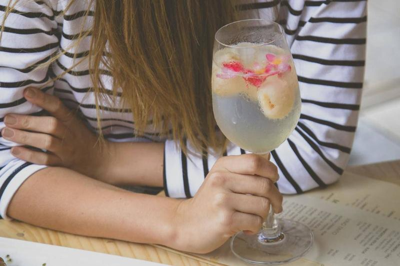 A woman holds a glass of sparkling water and fruit.