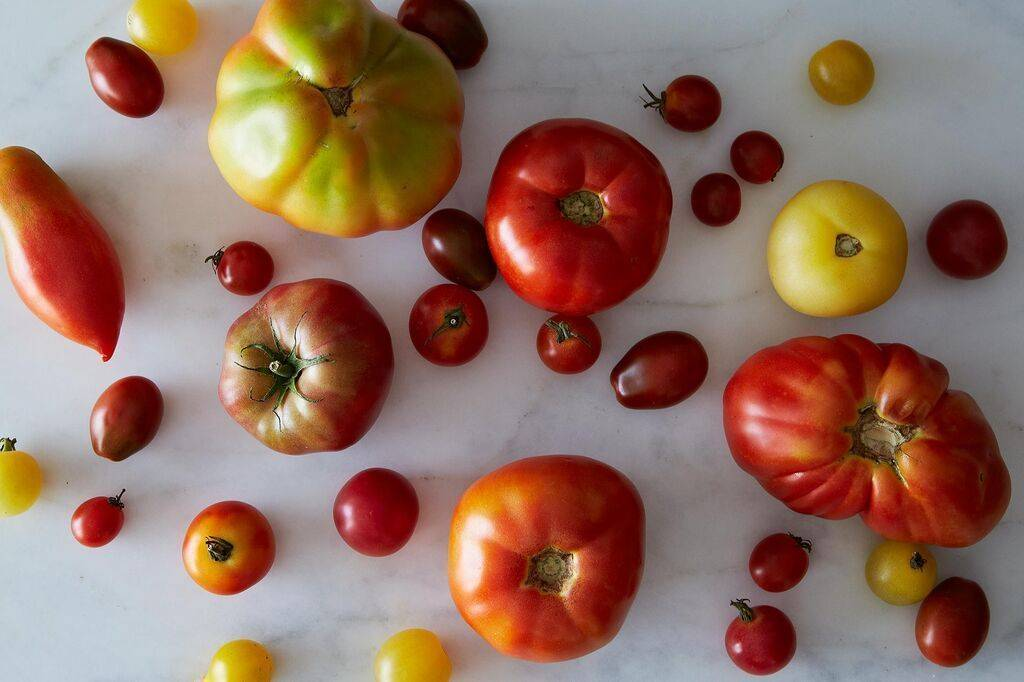 Tomatoes sit on a baking sheet with their stems facing down.