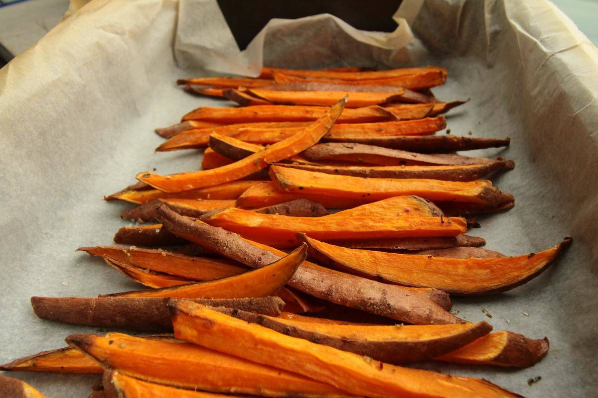 Sweet potato fries lie on a pan.