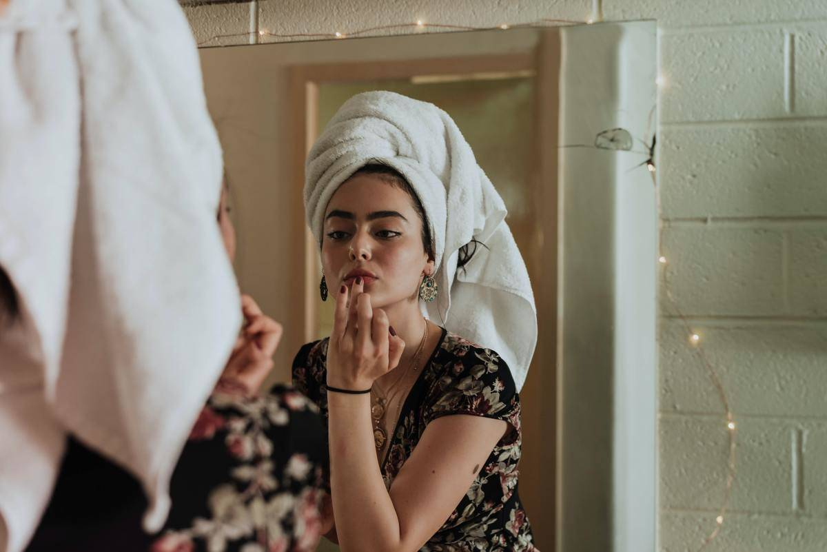 After a shower, a woman puts on makeup in the bathroom with a towel wrapped around her hair.