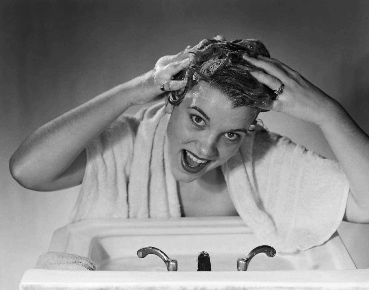 In this photo from the 1950s, a woman washes her hair with shampoo in the sink.