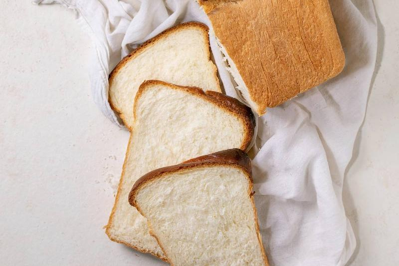 White bread slices lie next to a load and on top of a white cloth.