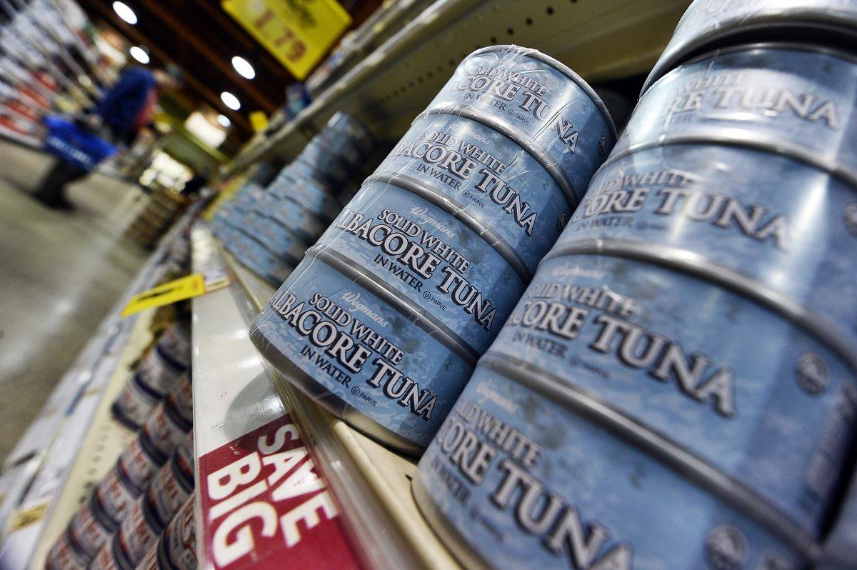 Cans of albacore tuna are stacked on grocery store shelves