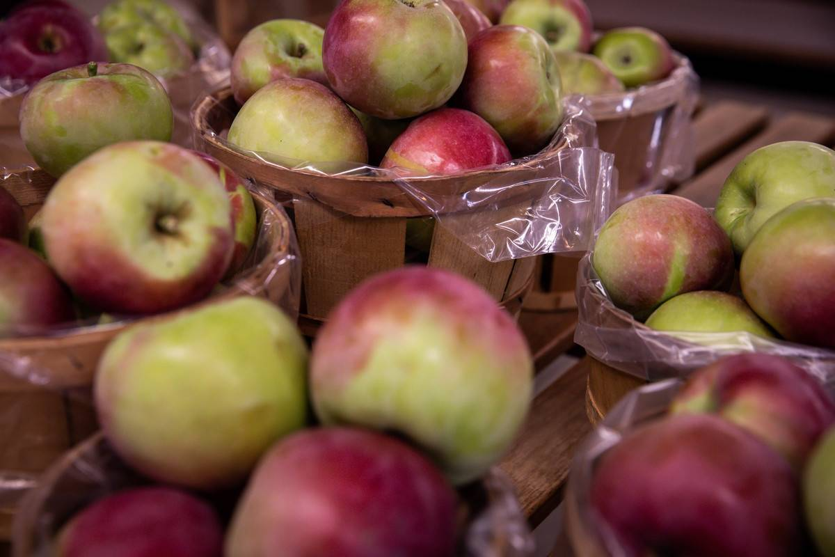 Apples are stored in baskets and plastic bags.