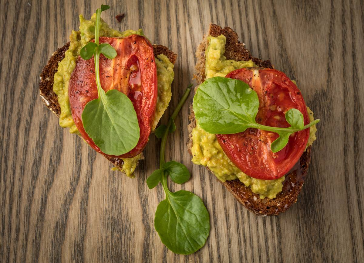Avocado toast is topped with roasted tomato and basil.