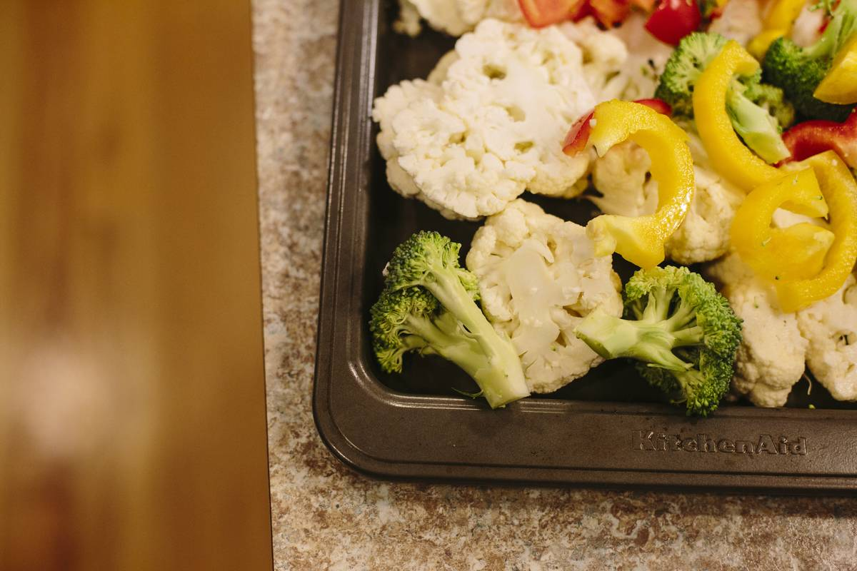 Cauliflower joins broccoli and peppers on a baking tray.