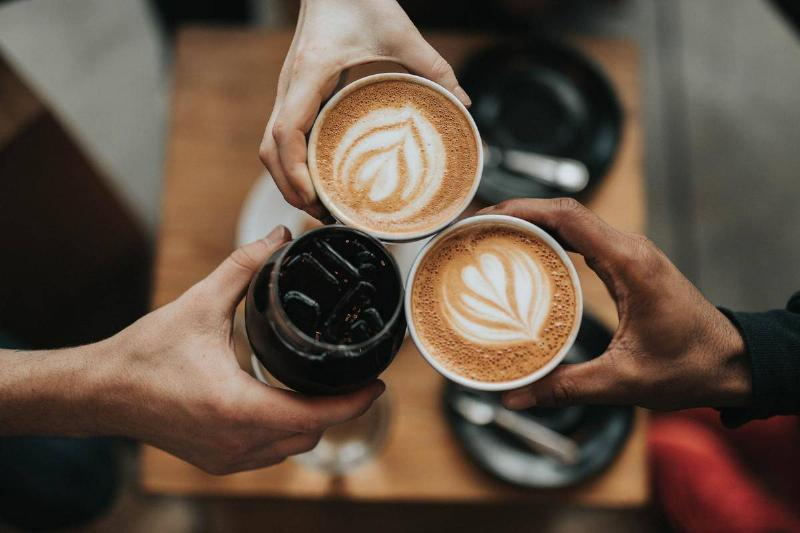 Three people press their coffee cups together to cheer.