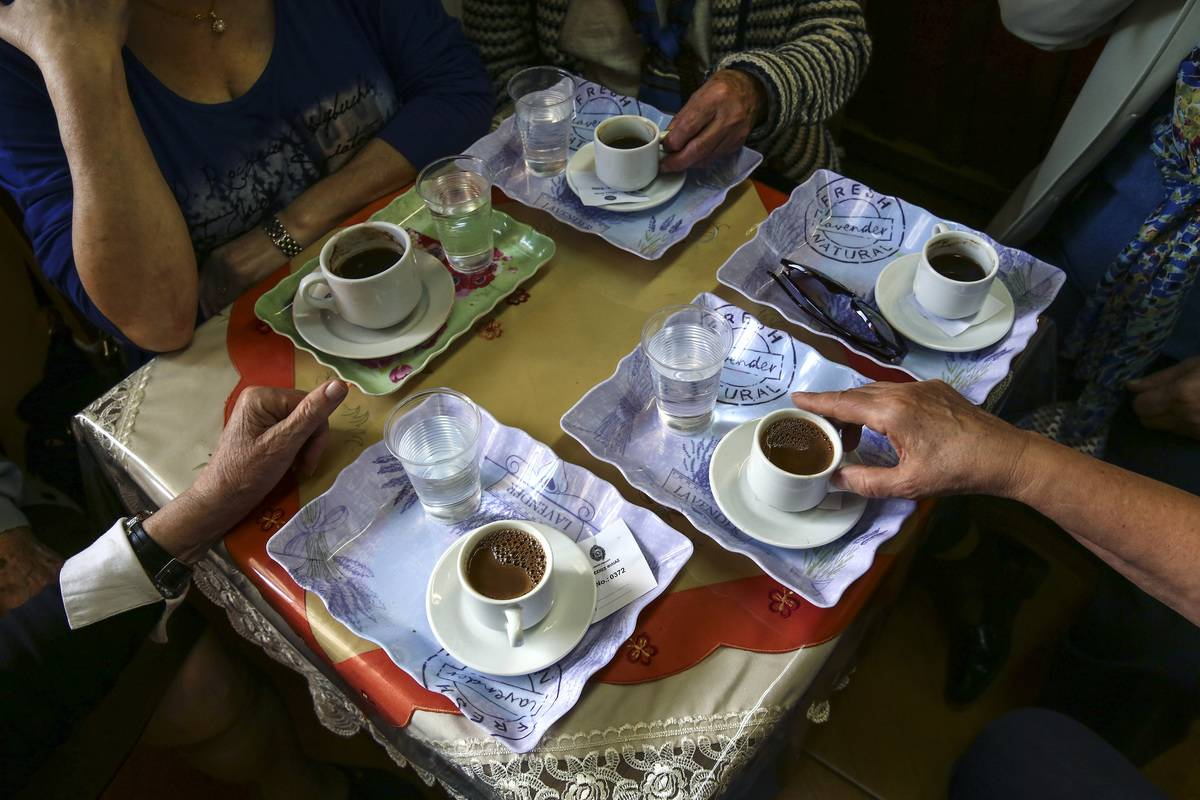 Five older adults sit at a cafe table and drink coffee together.