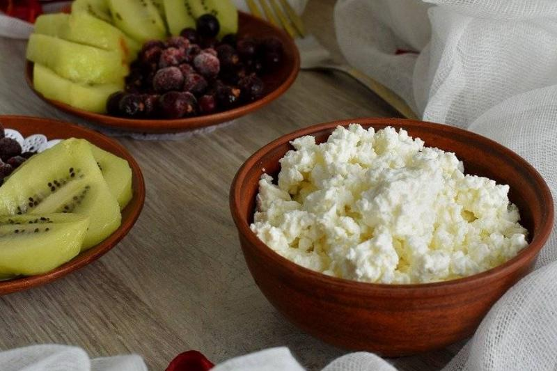 A wooden bowl holds cottage cheese.