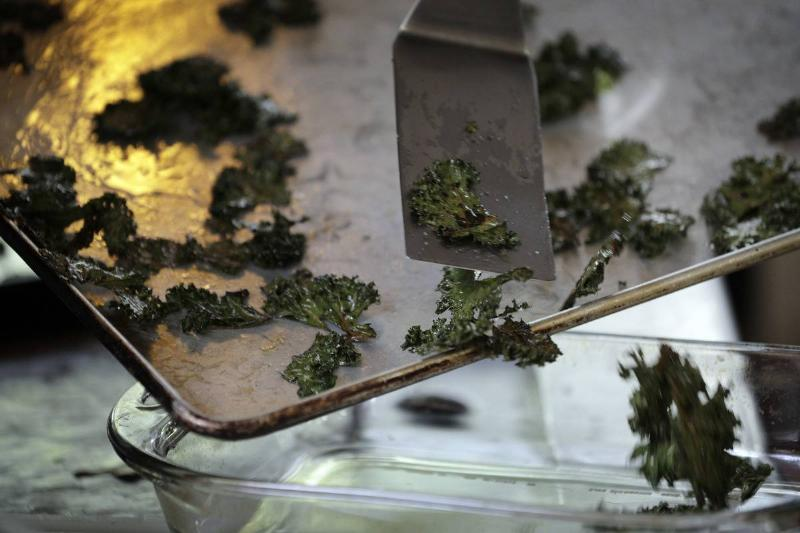 A chef dishes kale chips from a baking pan into a glass container.