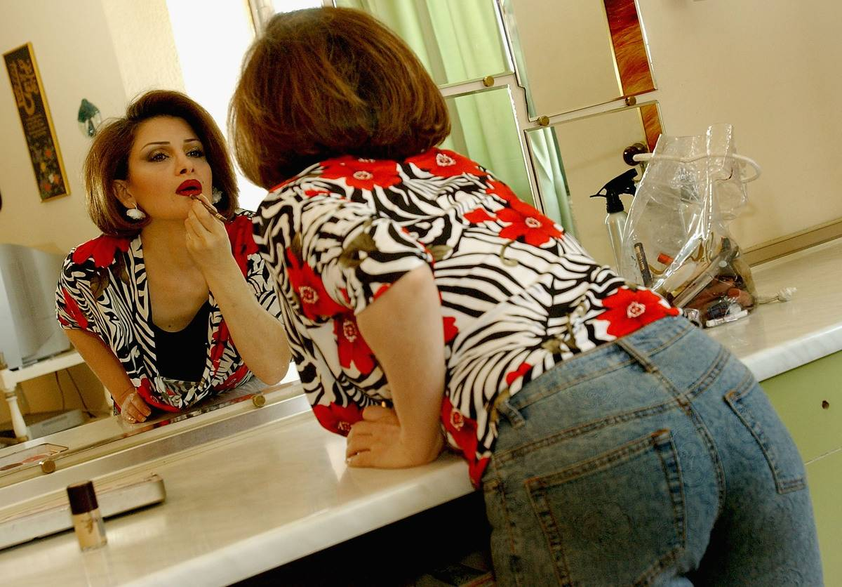 A woman applies lip liner while looking in her bathroom mirror.
