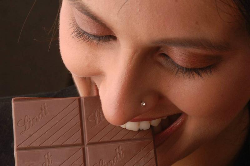 A woman bites squares of dark chocolate.