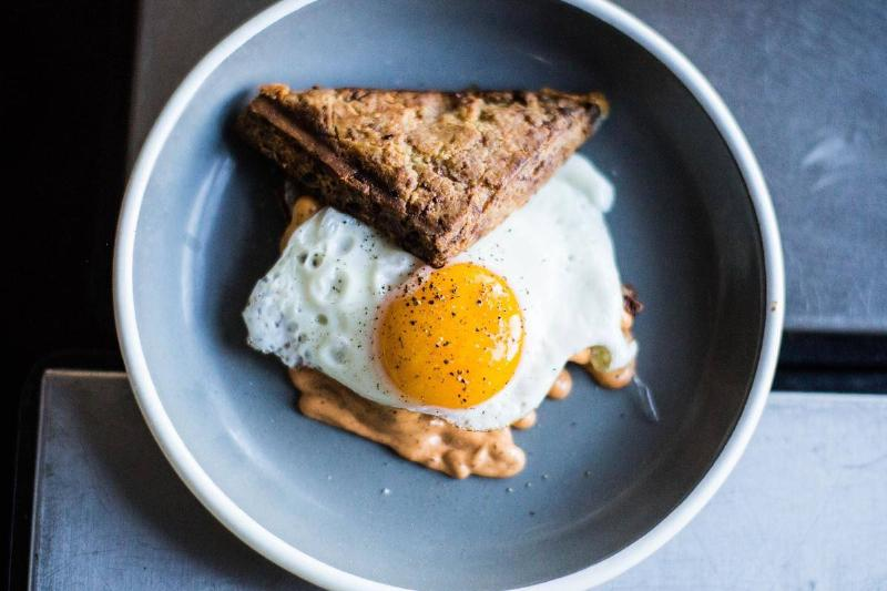 A sunny-side-up egg is on top of toast and peanut butter.