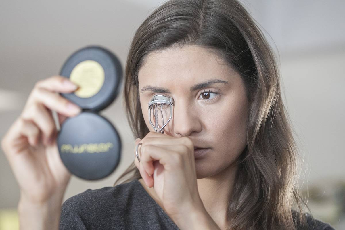 A woman curls her eyelashes while looking into a small handheld mirror.
