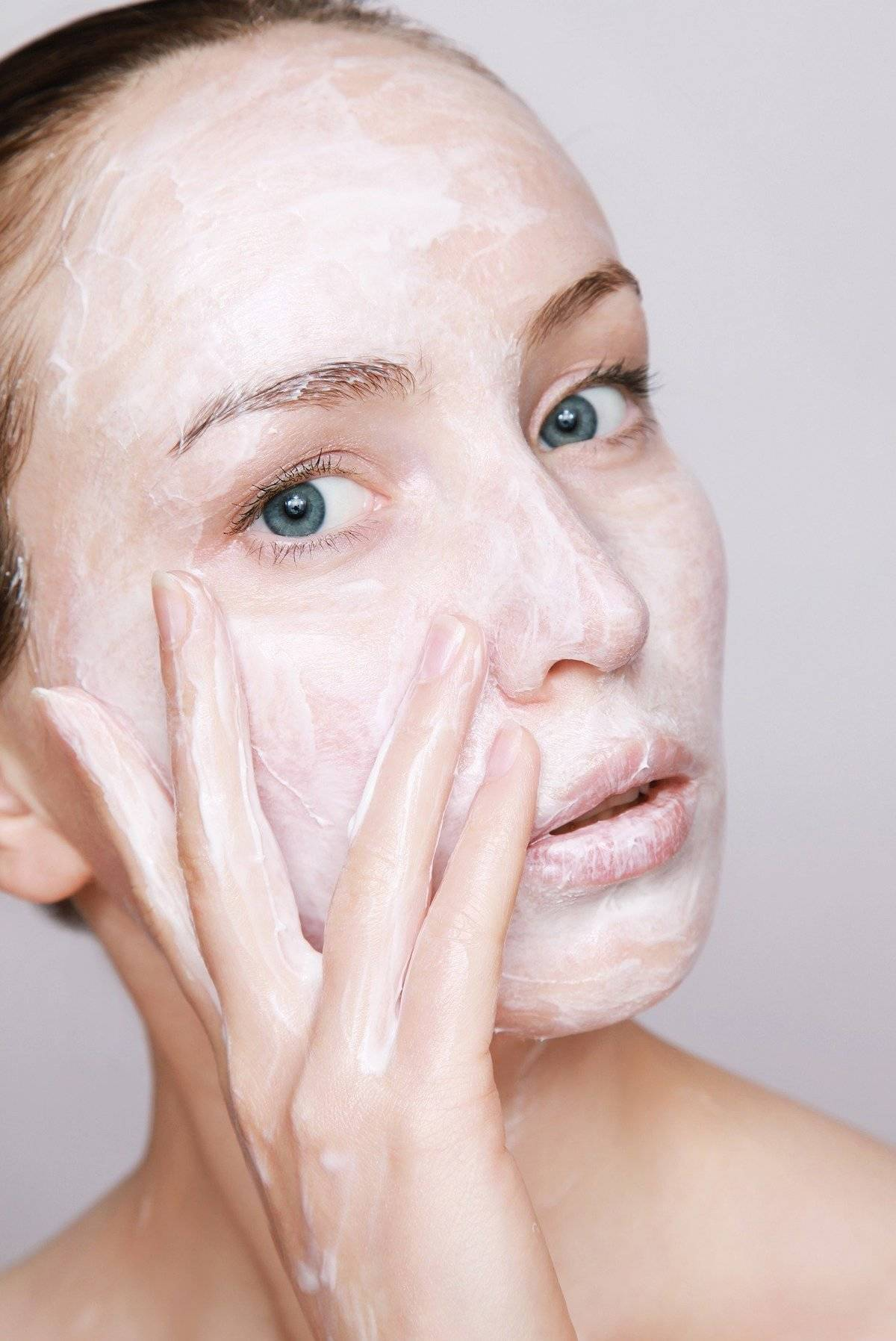 A woman has lotion all over her face.