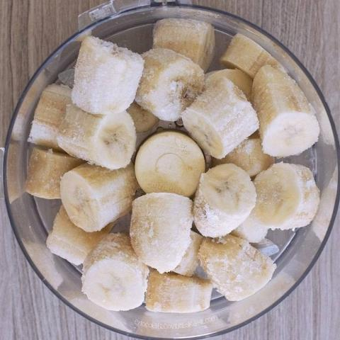A glass bowl holds frozen banana slices.