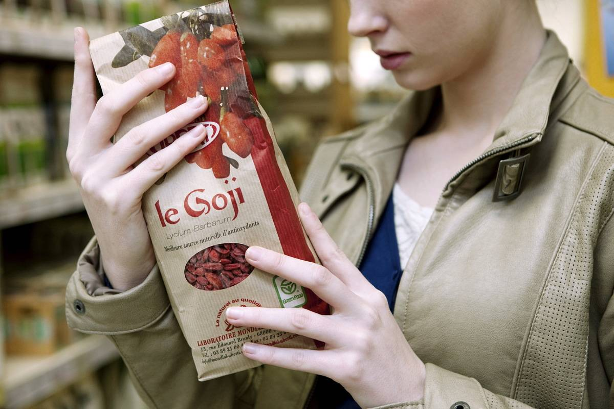 A woman holds up a bag of goji berries in an organic supermarket.