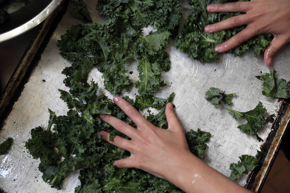 A woman rubs kale with olive oil before putting it on a baking pan.