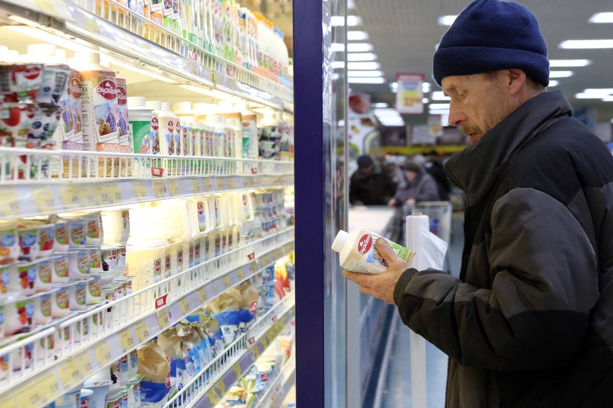 A man picks up a container of kefir while grocery shopping.