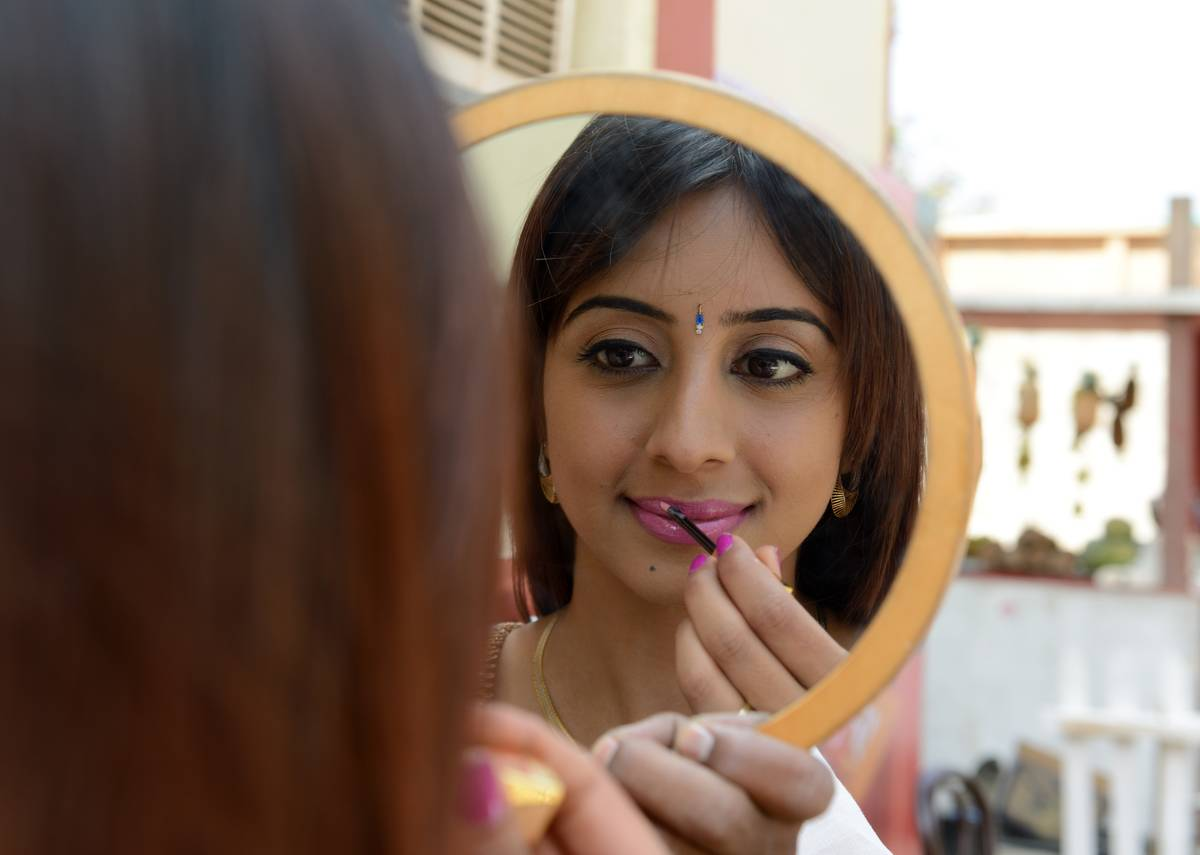 An Indian actress puts on her mirror by holding up a mirror outside.