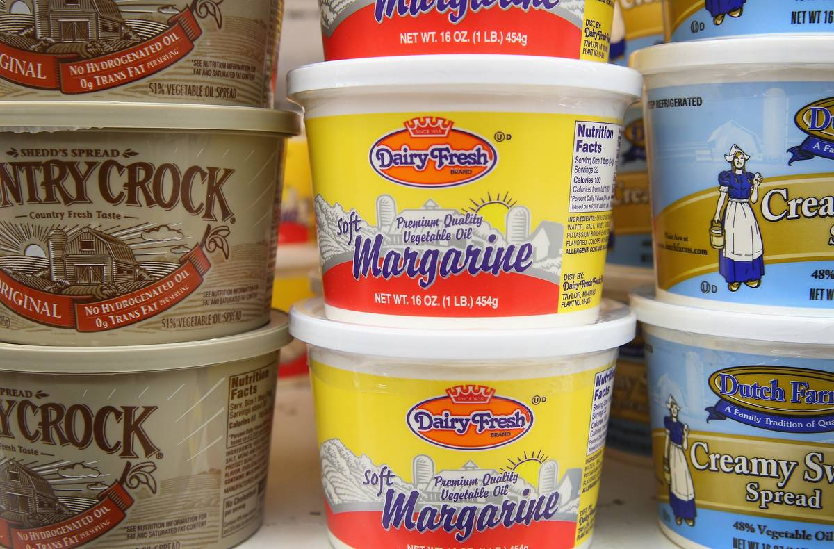 Tubs of margarine are stacked on top of each other in a supermarket.