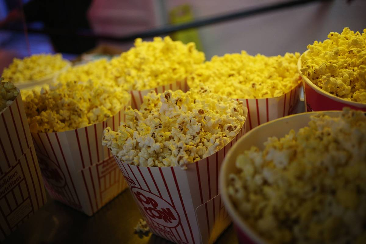Containers of buttered popcorn are ready to buy in a movie theater.