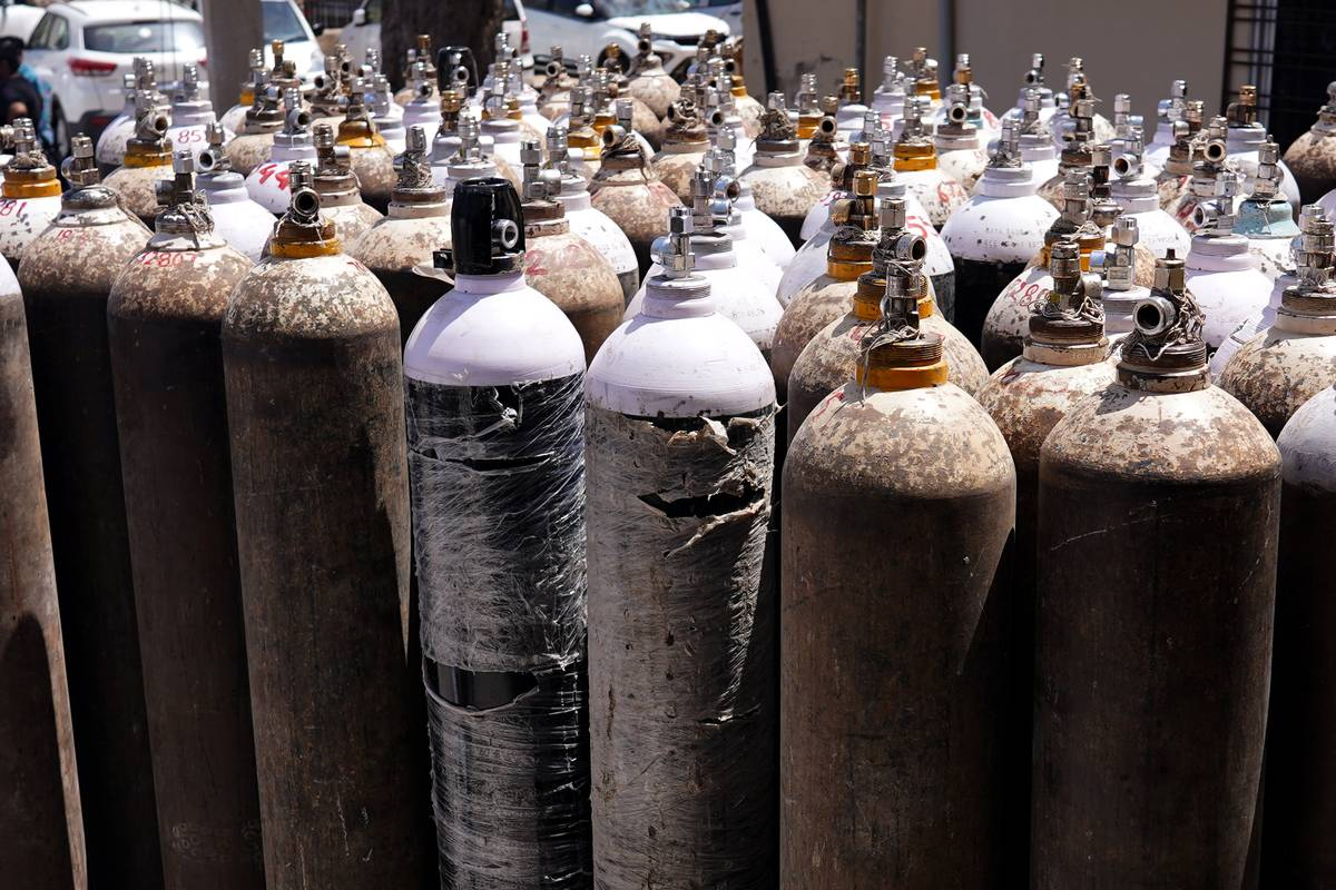 Medical oxygen cans are lined in rows outside of a hospital.