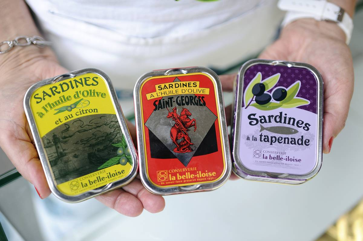A chef holds out three different cans of sardines.