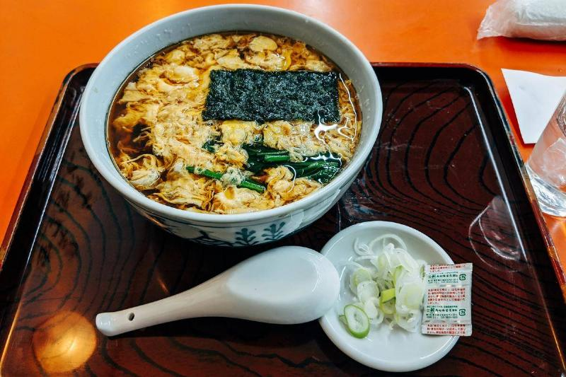 Dried seaweed floats on top of ramen in a bowl.