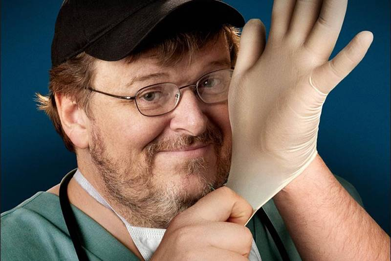 Michael Moore putting a rubber glove on in Sicko