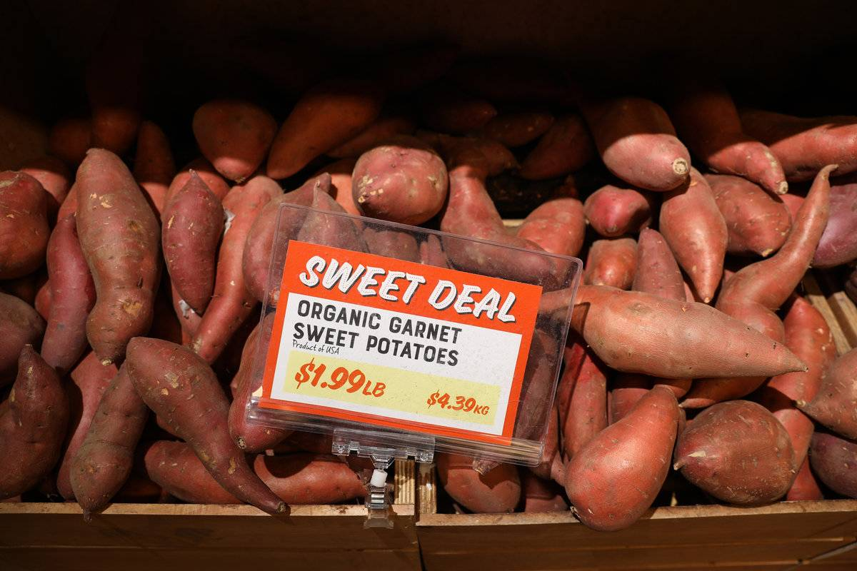 A sign for sweet potatoes on sale says