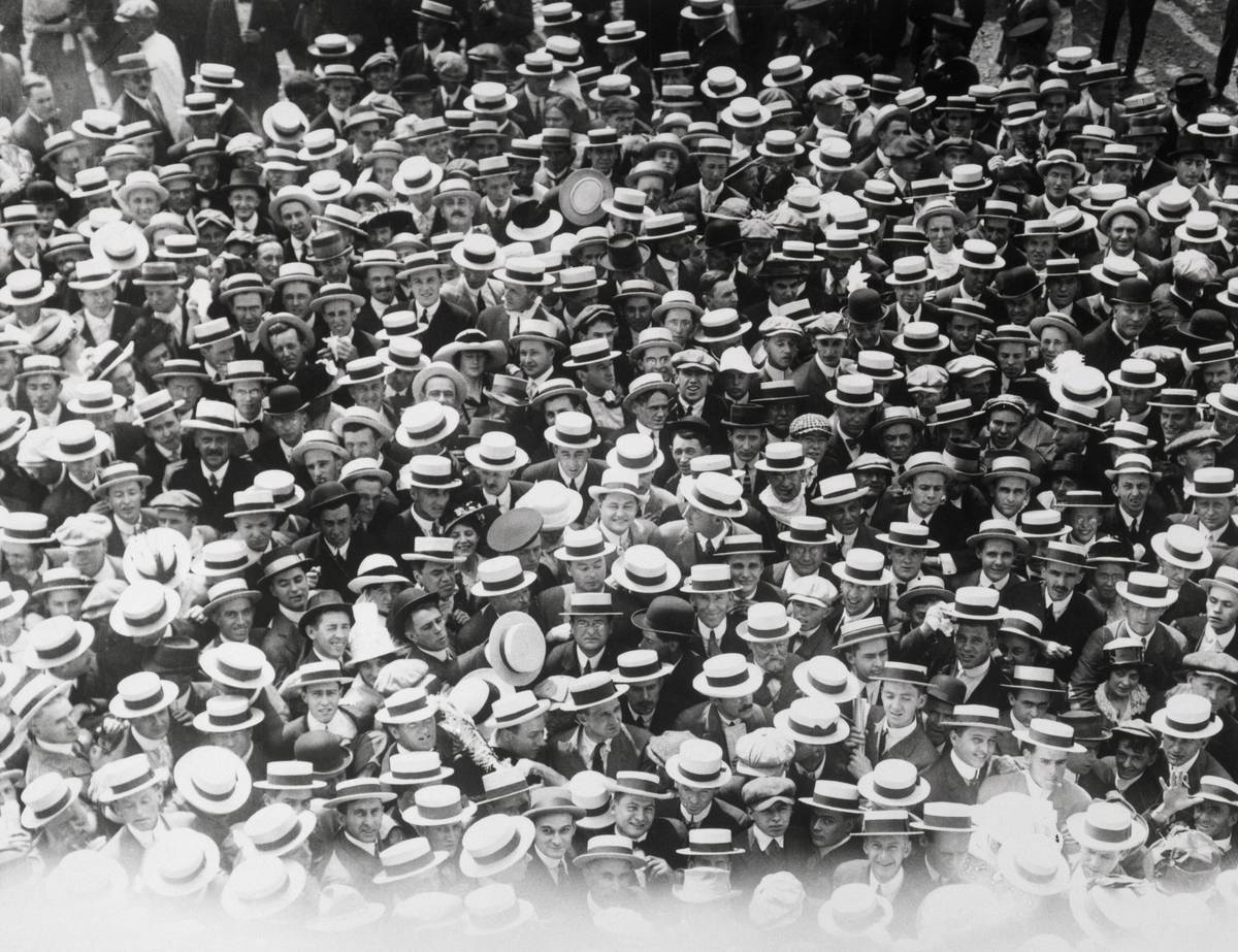 In the 1920s, people wearing hat crowd a baseball games.