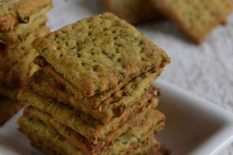 Whole wheat crackers are stacked on a square plate.