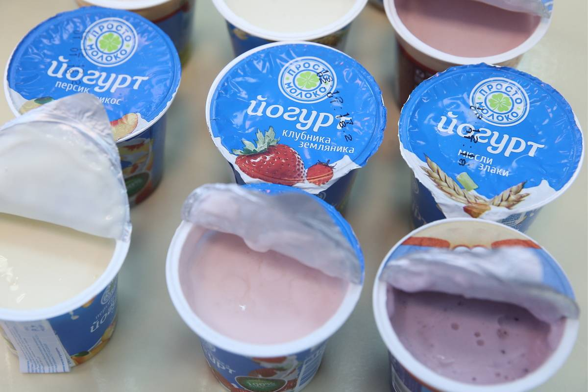 A variety of yogurt containers have their lids open.