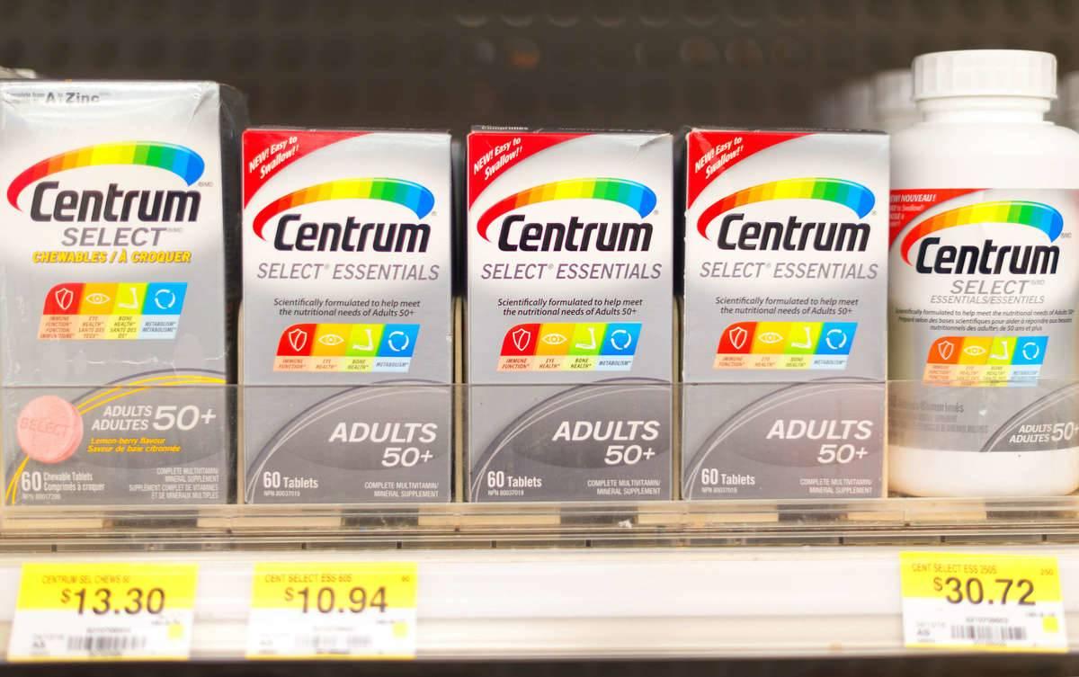 Centrum vitamin bottles are stacked on store shelves.