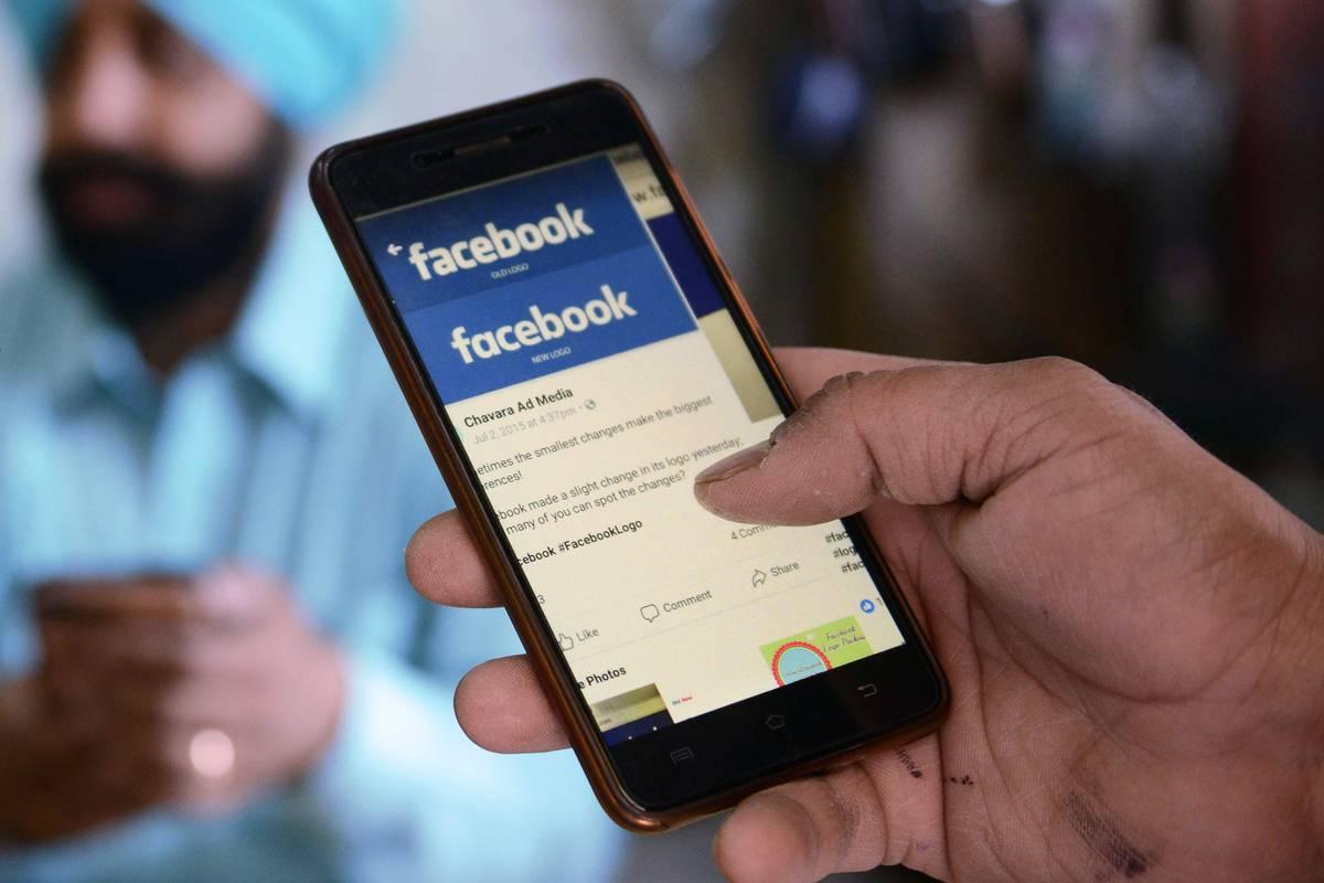 A man scrolls through the Facebook app on his phone.