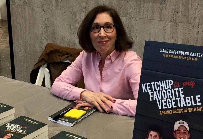 Liane sits at a booth to provide autographs for her book.