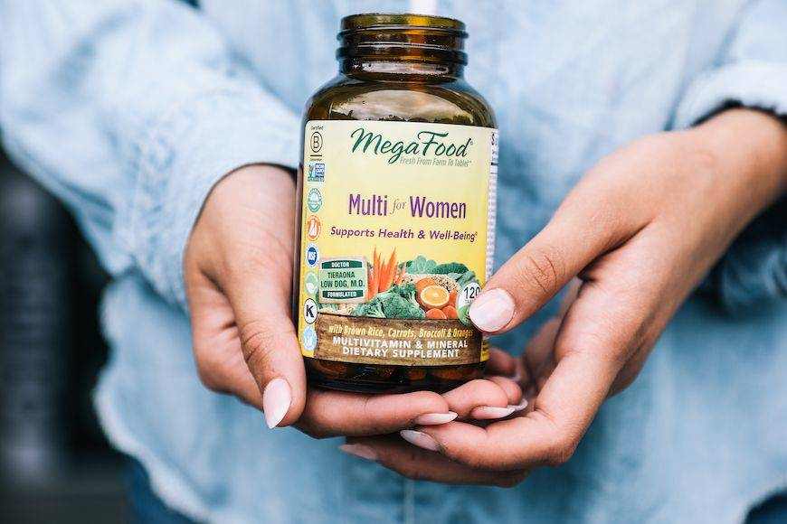 A woman holds a container of MegaFood Multi vitamins for women.