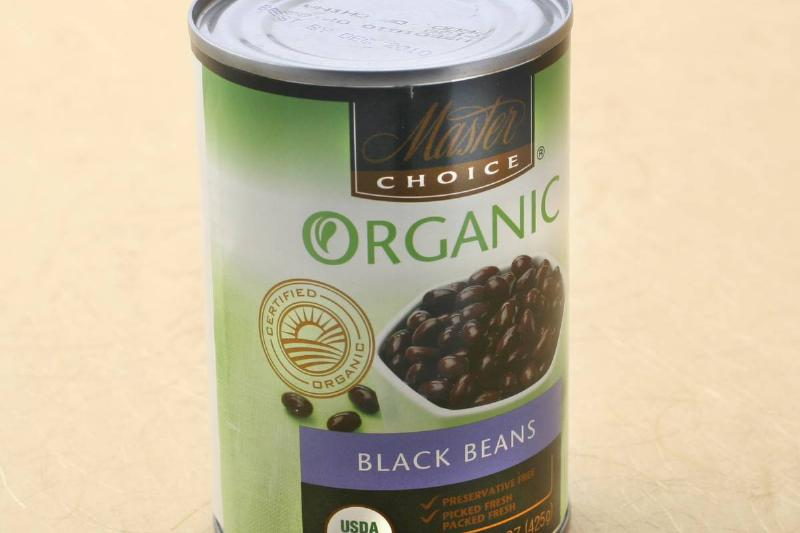 A can of black beans is on a table.
