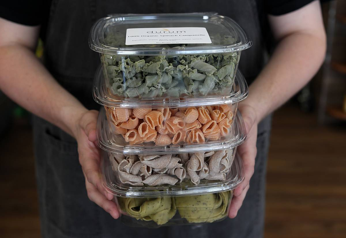 An employee holds containers of dried, boxed pasta at a pasta retail shop.