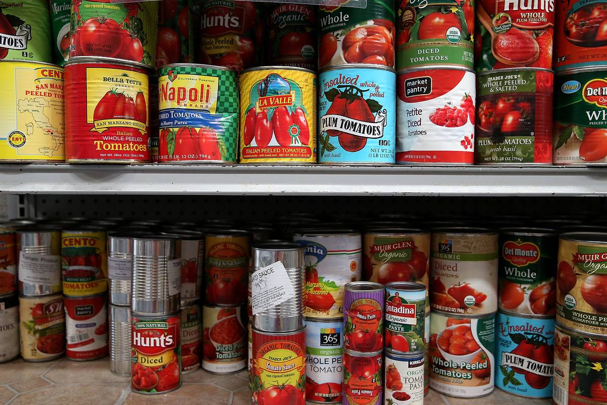 A pantry is filled with shelves of canned tomatoes.