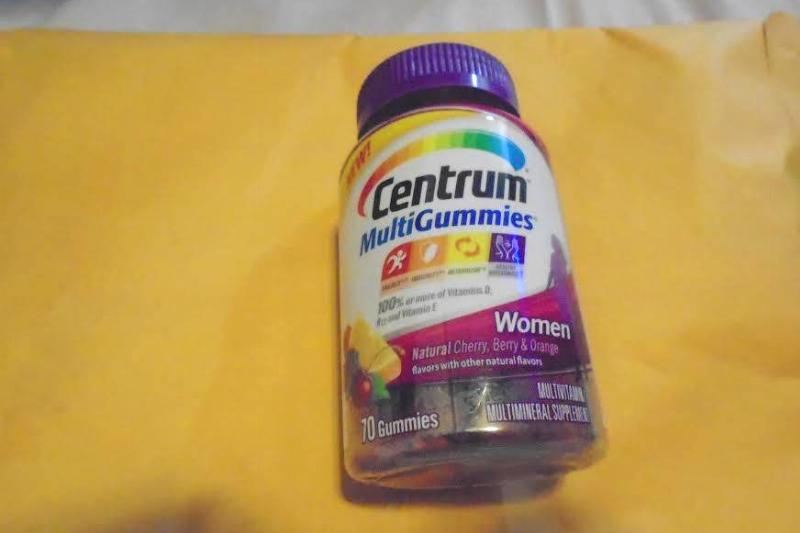 A bottle of Centrum gummy vitamins lies on a yellow sheet of paper.